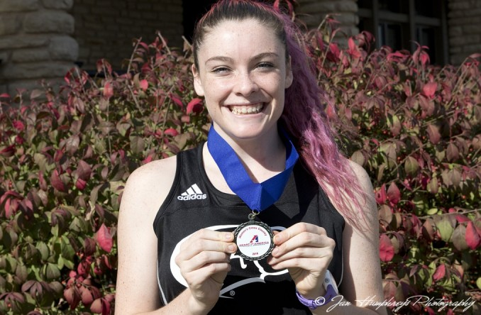 Freshman Penny Fenn poses with her 10th place medal at the Heart XC Championships Saturday at Swope Park.